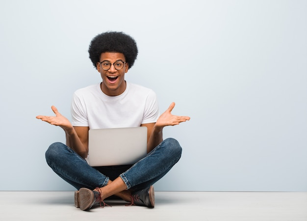 Young black man sitting on the floor with a laptop celebrating a victory or success