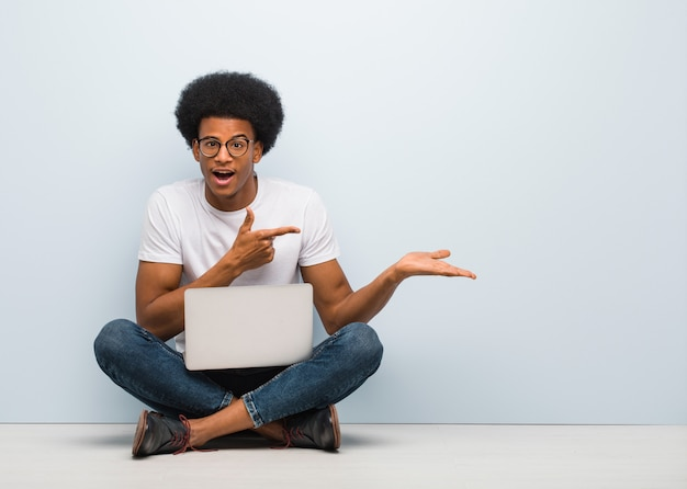 Young black man sitting on the floor with a laptop holding something with hand