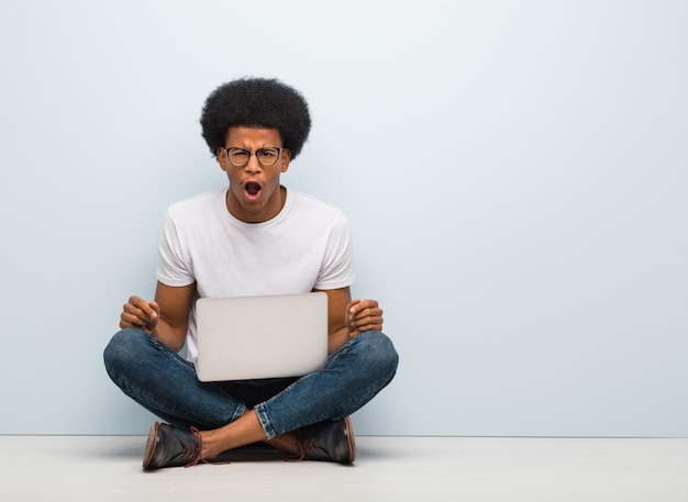 Young black man sitting on the floor with a laptop screaming very angry and aggressive