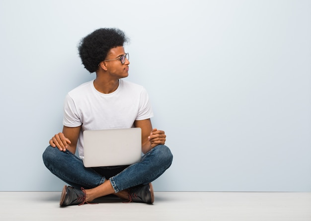 Young black man sitting on the floor with a laptop on the side looking to front