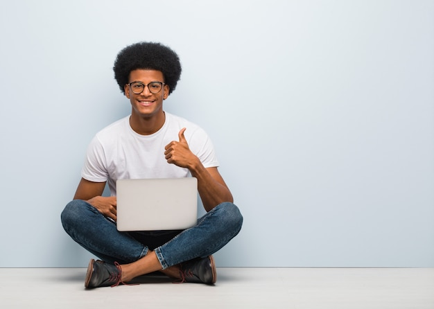 Young black man sitting on the floor with a laptop smiling and raising thumb up