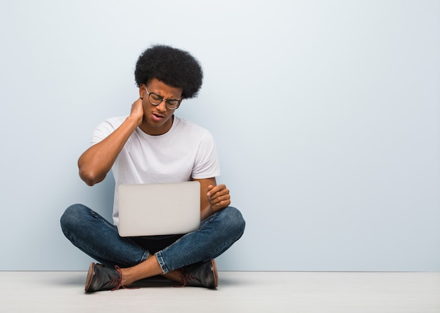 Young black man sitting on the floor with a laptop suffering neck pain