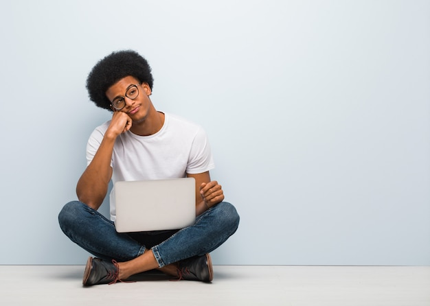 Young black man sitting on the floor with a laptop thinking of something, looking to the side