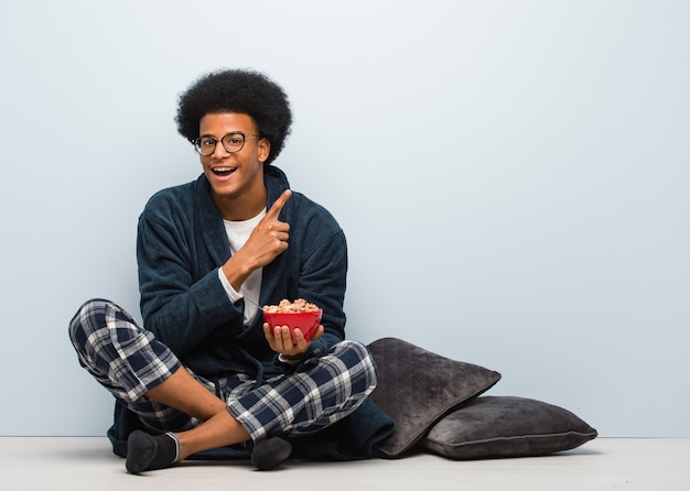 Young black man sitting and having a breakfast pointing to the side with finger