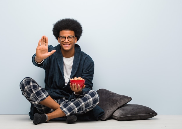 Young black man sitting and having a breakfast putting hand in front