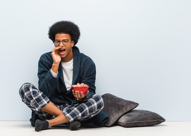 Young black man sitting and having a breakfast shouting something happy to the front