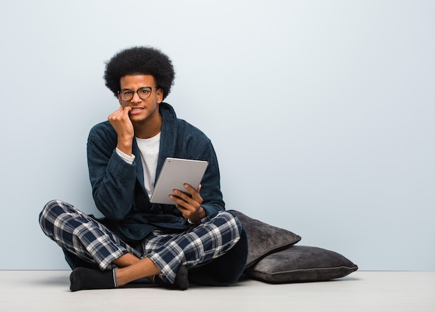 Young black man sitting on his house and holding his tablet biting nails, nervous and very anxious
