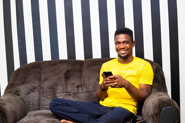 온라인 뱅킹으로 온라인 청구서를 지불하는 모바일 장치를 사용하여 거실에 앉아 있는 젊은 흑인 남성