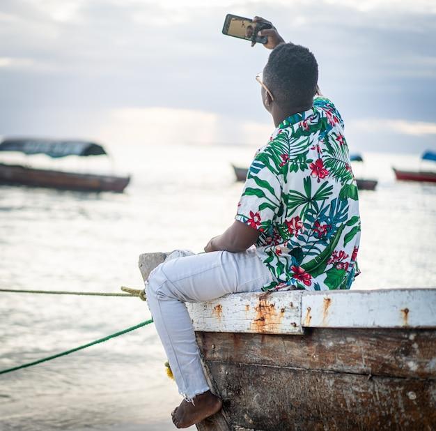 Молодой темнокожий мужчина сидит на лодке и делает селфи в одиночестве