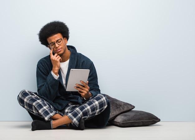 젊은 흑인 남자가 그의 집에 앉아 의심하고 혼란스러워하는 그의 태블릿을 들고