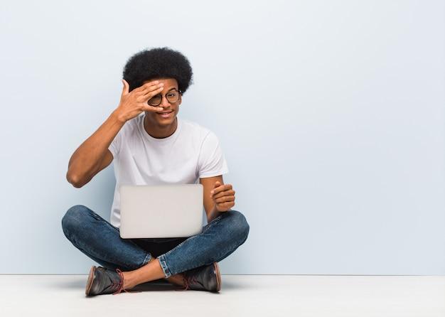젊은 흑인 남자가 노트북과 함께 바닥에 앉아 당황하고 동시에 웃고