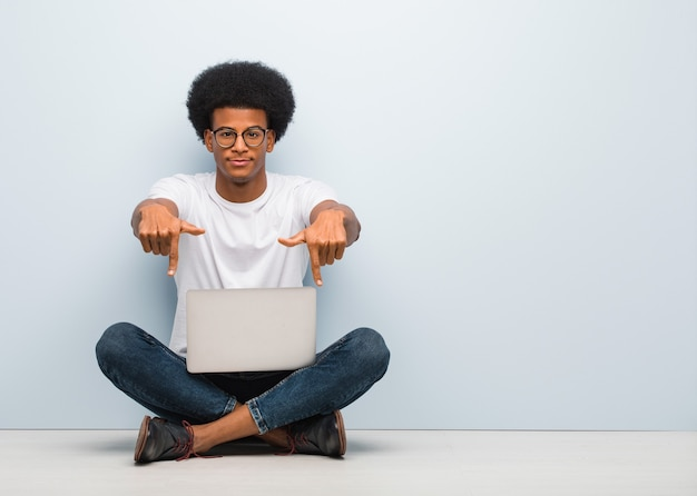 Молодой черный человек сидит на полу с ноутбуком, указывая пальцами вниз