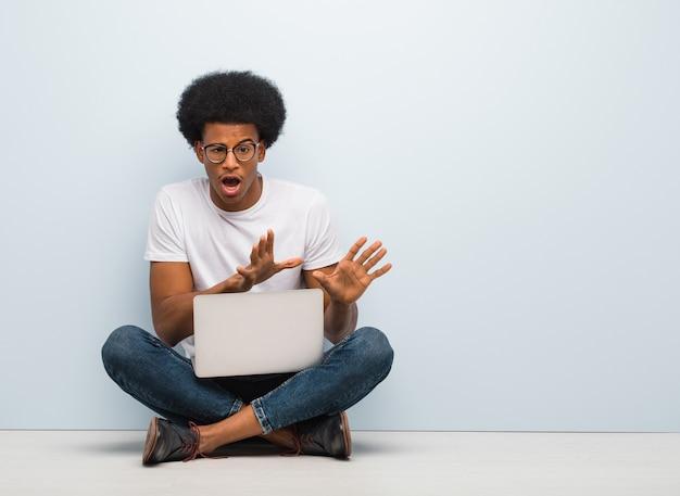 Молодой темнокожий мужчина сидит на полу с ноутбуком, отвергая что-то, делая жест отвращения