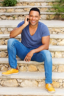 Young black man sitting on steps outside and talking on mobile phone