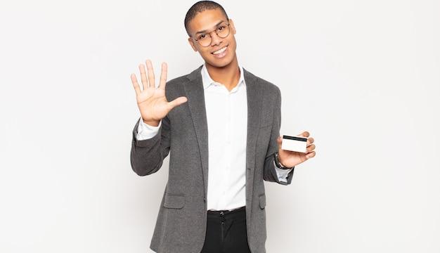 젊은 흑인 남자가 미소하고 친절하게보고, 앞으로 손으로 5 번 또는 5 번을 보여주는, 카운트 다운
