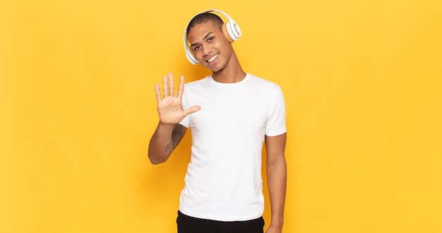 若い黒人男性は笑顔でフレンドリーに見え、手を前に向けて5番または5番を示し、カウントダウンします