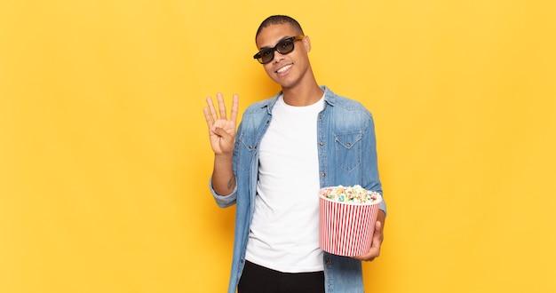 Молодой темнокожий мужчина улыбается и выглядит дружелюбно, показывает номер четыре или четвертый с рукой вперед, считая