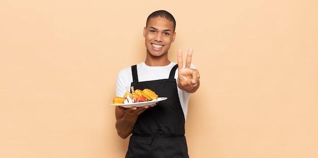 笑顔で幸せそうに見える若い黒人男性、のんきで前向きで、片手で勝利または平和を身振りで示す