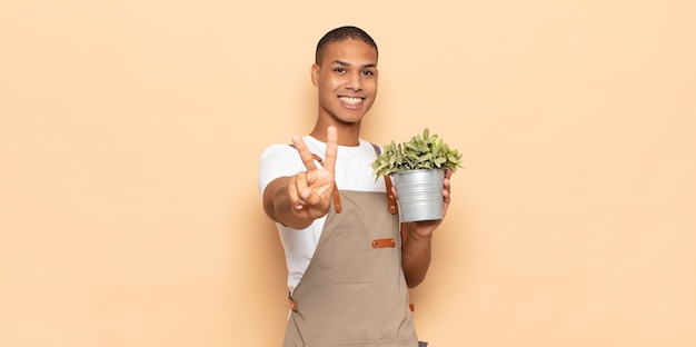 젊은 흑인 남자가 웃고 행복하고 평온하고 긍정적 인 찾고 한 손으로 승리 또는 평화를 몸짓으로합니다.