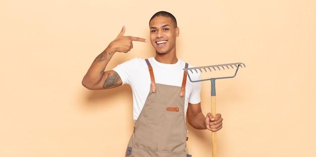 자신의 넓은 미소, 긍정적이고 편안하고 만족스러운 태도를 자신있게 가리키는 젊은 흑인 남자
