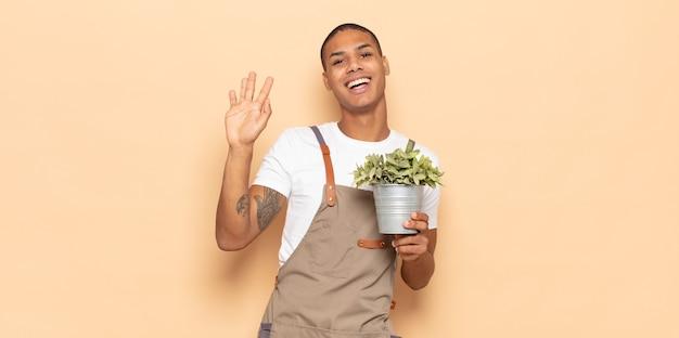 행복하고 유쾌하게 웃고, 손을 흔들고, 환영하고 인사하거나, 작별 인사를하는 젊은 흑인 남자