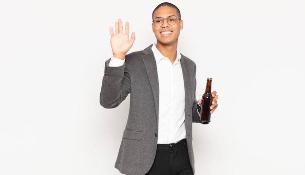 喜んで元気に笑って、手を振って、あなたを歓迎して挨拶するか、さようならを言う若い黒人男性