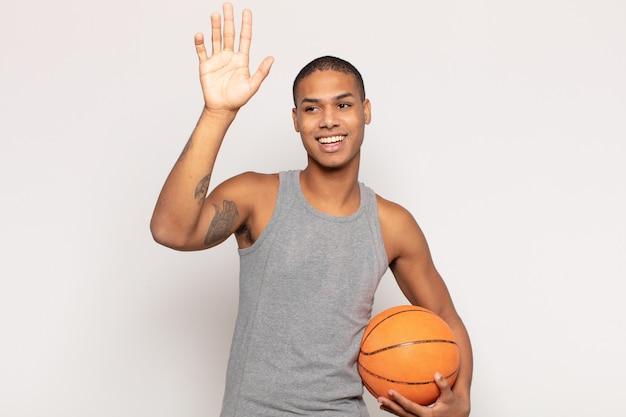 幸せで元気に笑って、手を振って、あなたを歓迎して挨拶するか、さようならを言う若い黒人男性