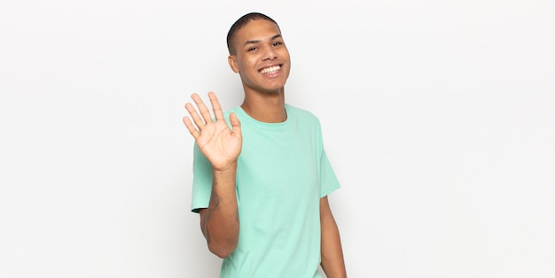 Young black man smiling happily and cheerfully, waving hand, welcoming and greeting you, or saying goodbye