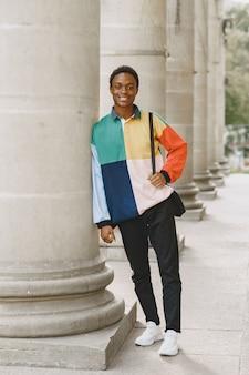 都会で笑っている若い黒人男性。カラフルなセーターの混血。