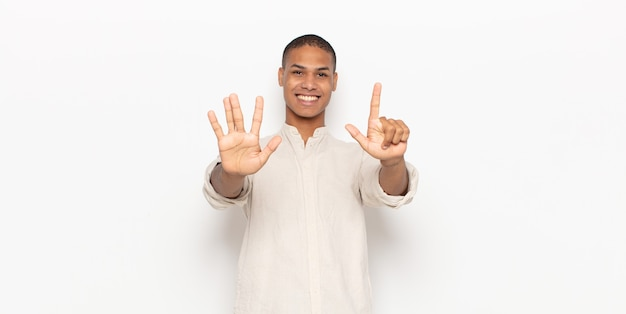 Young black man smiling and looking friendly, showing number seven or seventh with hand forward, counting down