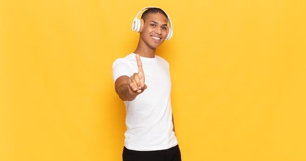Молодой темнокожий мужчина, гордо и уверенно улыбаясь, триумфально принимает позу номер один, чувствуя себя лидером