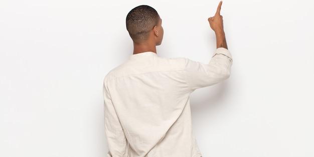 立ってオブジェクトを指している若い黒人男性