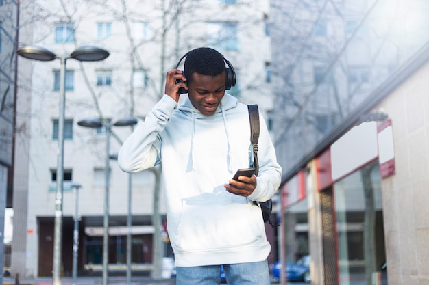 Young black man standing in the street while listening music by headphones