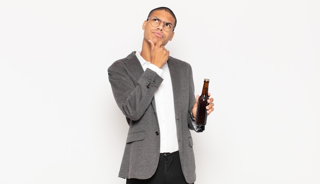 若い黒人男性が考え、疑わしくて混乱し、さまざまな選択肢があり、どの決定を下すか疑問に思っています