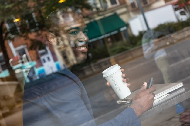 Young black man typing on mobile and drinking coffee