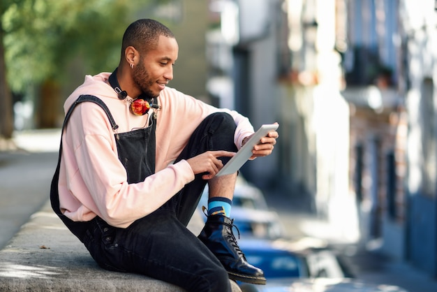 Young black man using digital tablet in the city