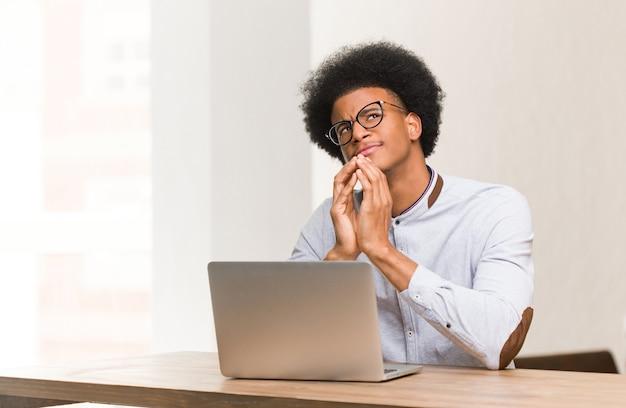 Молодой черный человек, используя свой ноутбук, разрабатывая план