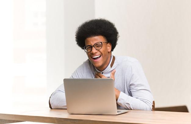Young black man using his laptop laughing and having fun