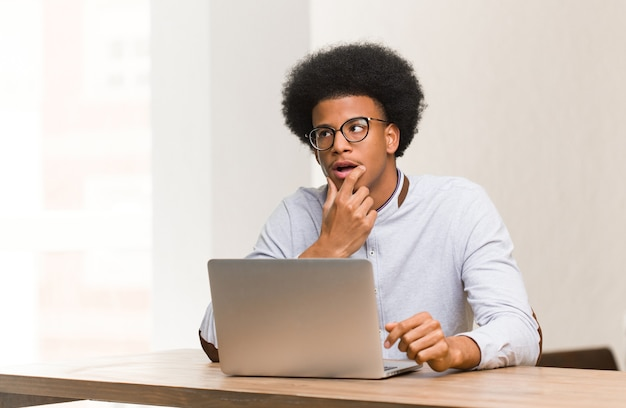 Young black man using his laptop relaxed thinking about something looking at a copy space