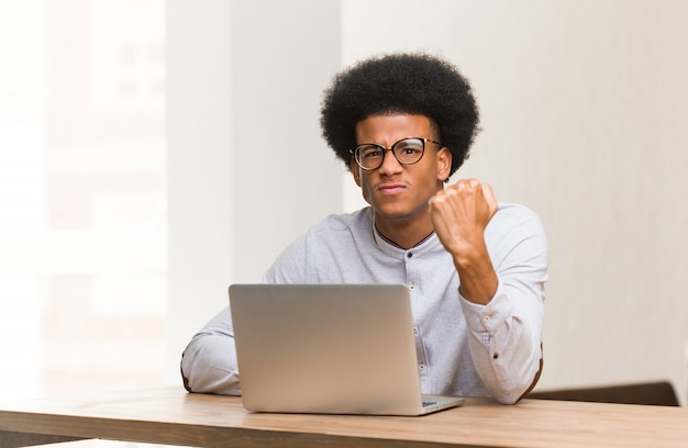 Young black man using his laptop showing fist to front, angry expression