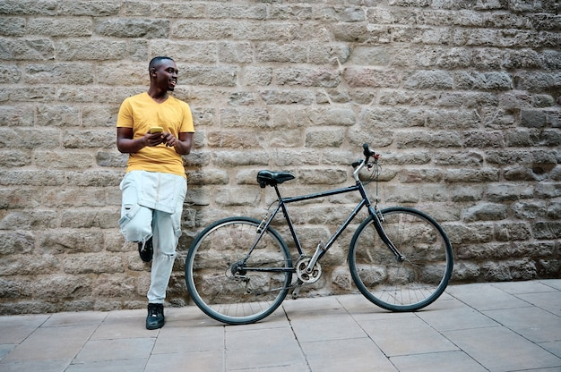 Young black man using his smartphone with bike