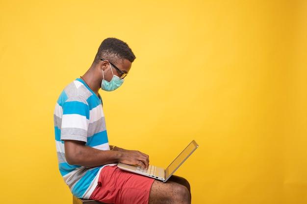 Молодой темнокожий мужчина в маске и очках с помощью ноутбука, вид сбоку