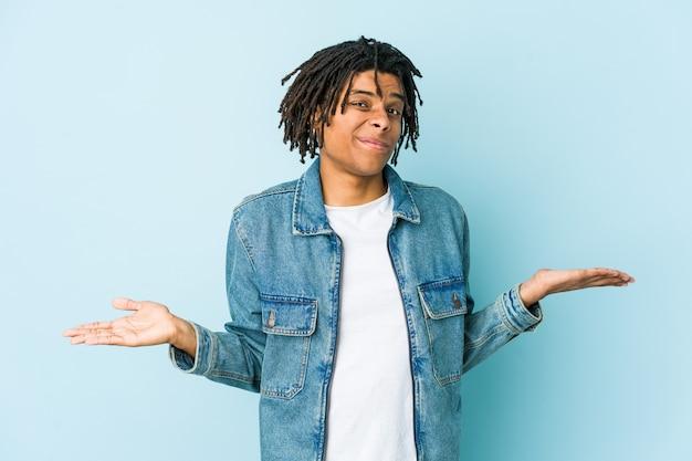 ジェスチャを疑って肩をすくめるジーンズのジャケットを着た若い黒人男性。