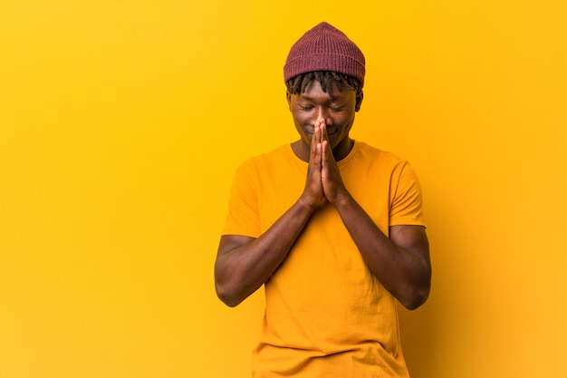 Young black man wearing dreads holding hands in pray near mouth, feels confident.