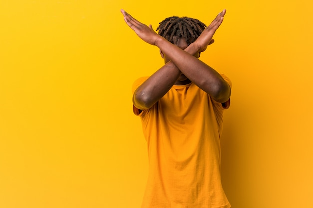 Young black man wearing dreads keeping two arms crossed, denial concept.