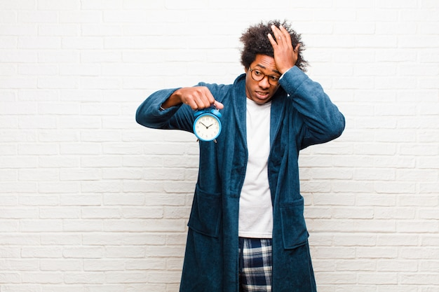 Young black man wearing pajamas with an alarm clock