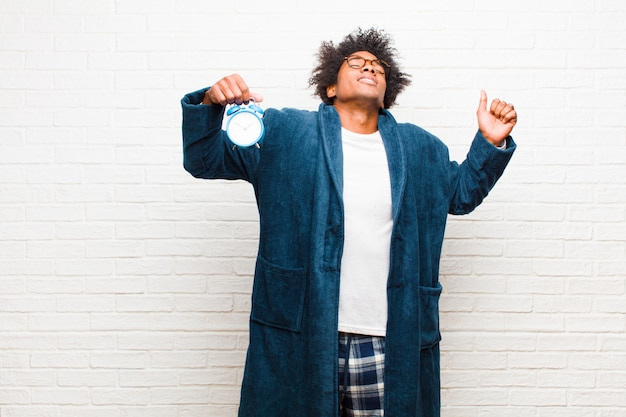Young black man wearing pajamas with an alarm clock