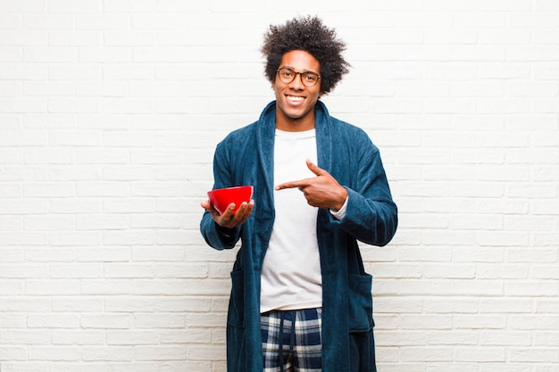 Young black man wearing pajamas with a breakfast bowl against br