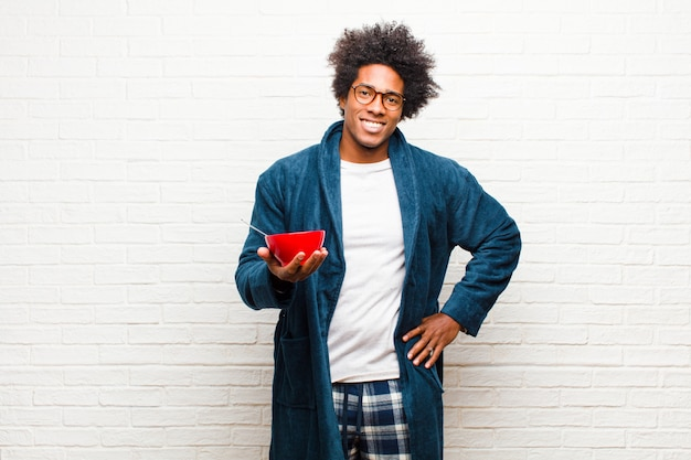 Young black man wearing pajamas with a breakfast bowl