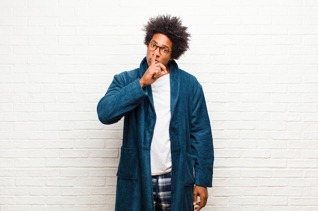 Young black man wearing pajamas with gown asking for silence and quiet, gesturing with finger in front of mouth, saying shh or keeping a secret against brick wall